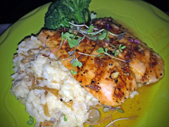Sweet Chili Pomegranate Glazed Salmon: Wild Norwegian salmon filet glazed with a slightly spicy and sweet sauce served over caramelized onion-pea risotto and served with the local vegetable of the day