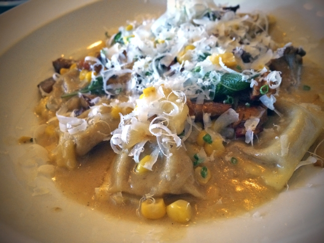 Sweet corn agnolotti in corn broth with cippolini, pancetta and chantrelles