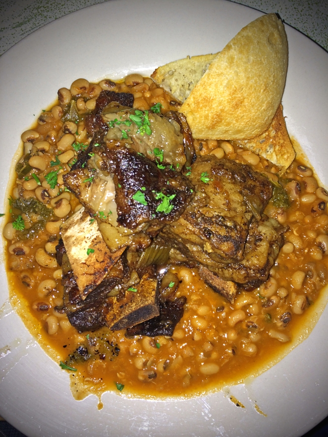 Sassafras Short Ribs – Slow braised, sassafras rubbed, local short ribs served with organic black eyed peas, tomato & Swiss chard stew and house-baked garlic bread