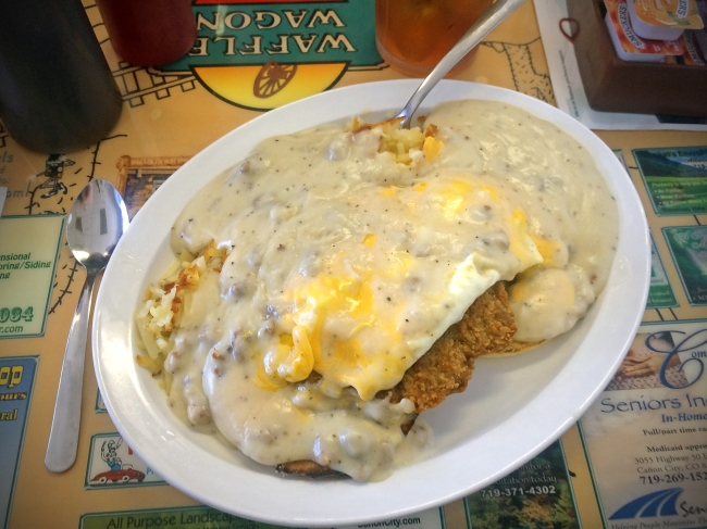 """""""Lester Special"""" toasted english muffin topped with chicken fried steak, hash browns, 2 eggs, cheese, and smothered in sausage gravy."""