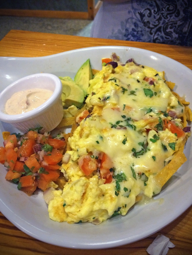 Migas: A Tex-Mex scramble featuring onions, tomatoes, cilantro, pepperjack cheese, spicy chorizo, garnished with sliced avocado, pico de gallo, chipotle sour cream and crispy tortilla chips