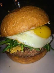 Sunny Side Burger: Parmesan frico, fried egg, truffle thyme compound butter, truffled arugula, truffled aioli